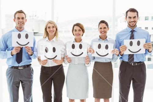 Business people holding happy smileys in office