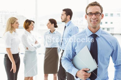 Smiling businessman with colleagues behind
