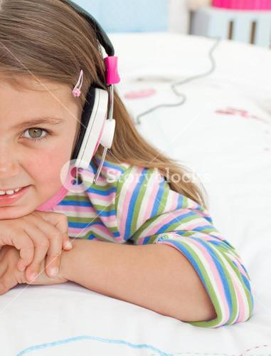 Little gril listening to music with headphones