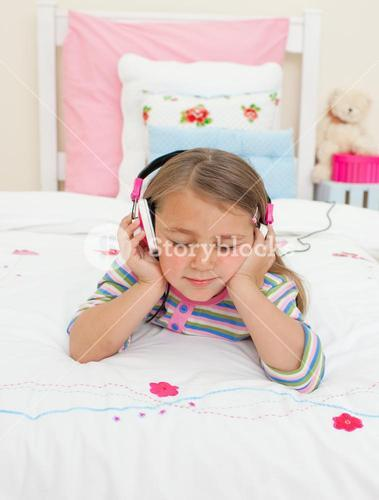 Beautiful Little gril listening to music lying on her bed