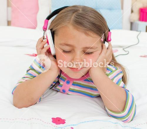 Close up of a Little gril listening to music with headphones