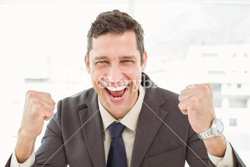 Cheerful businessman cheering in office