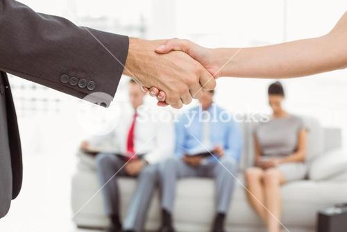 Handshake besides people waiting for interview