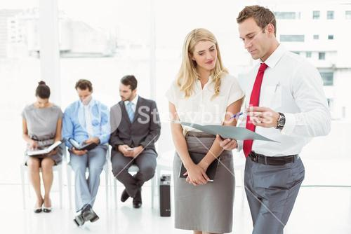 Businesspeople looking at file against people waiting for interview