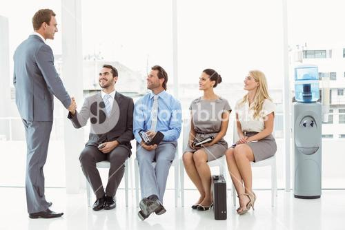 Businessman shaking hands with man besides people waiting for interview