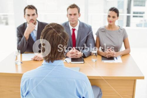 Business people interviewing man in office