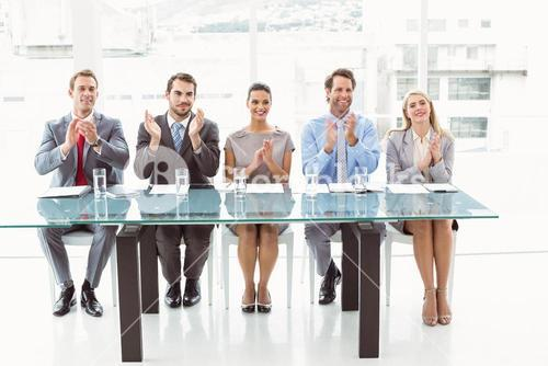 Interview panel clapping hands in office