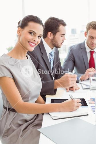 Business people writing notes in board room meeting