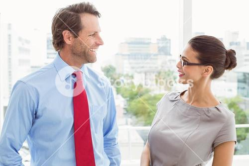 Business couple looking at each other in office