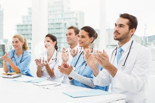 Doctors clapping hands in meeting