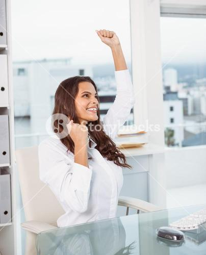 Cheerful businesswoman cheering in office