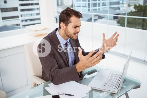 Frustrated businessman using laptop in office