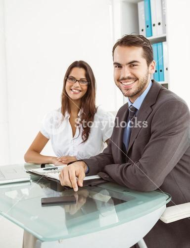 Smiling business people at office desk