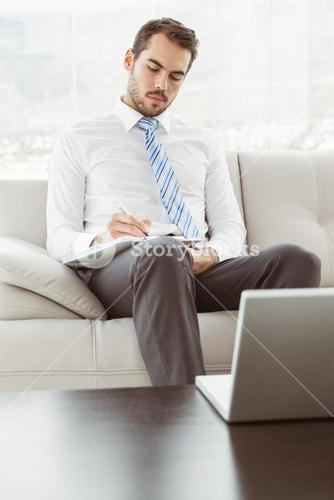 Businessman writing notes in living room