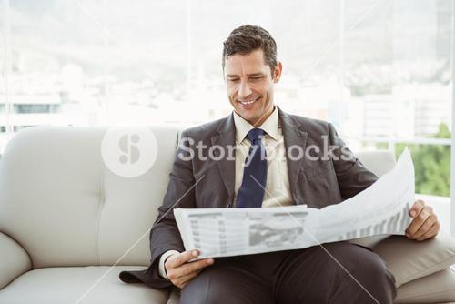 Businessman reading newspaper in living room