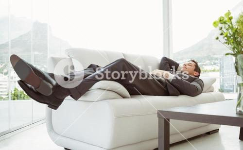 Young businessman lying on couch