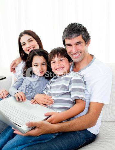 Jolly family using a laptop sitting on sofa
