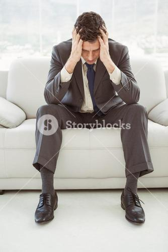 Worried businessman with head in hands sitting on couch