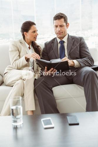 Businessman and secretary looking at diary in living room