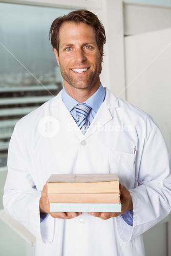 Smiling doctor holding books in medical office