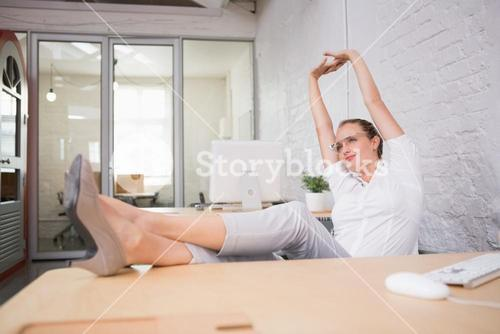 Businesswoman stretching while at work