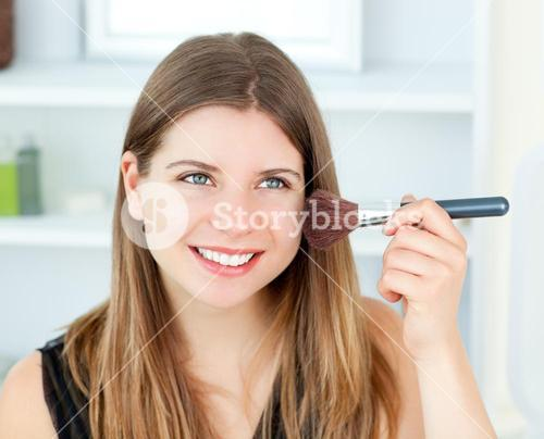 Portrait of a delighted woman using a powder brush against a white background