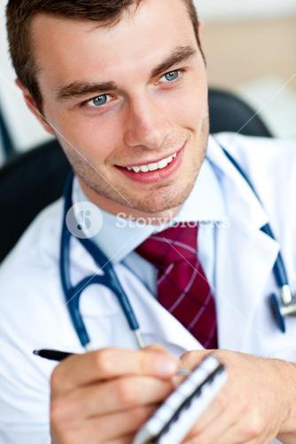 Attractive male doctor writing a perscription