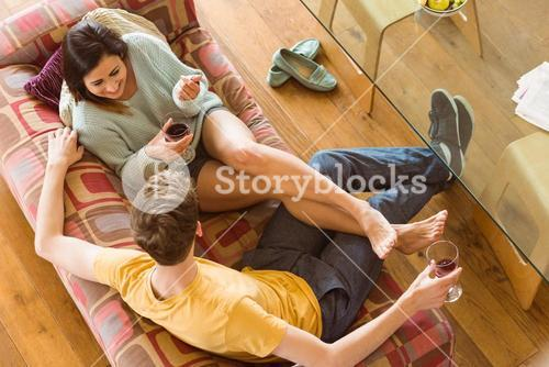 Young couple enjoying red wine on the couch