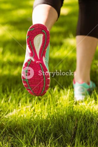 Woman in running shoes jogging on grass