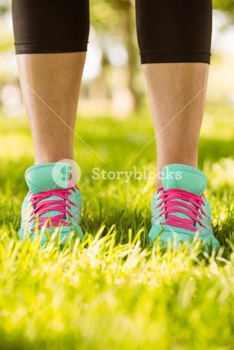 Woman in running shoes standing on grass
