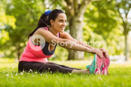 Happy fit brown hair stretching on the grass