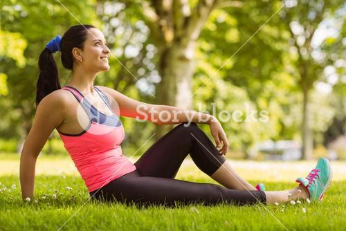 Cheerful fit brunette day dreaming on the grass
