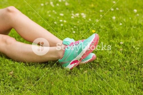 Woman in running shoes lying on grass