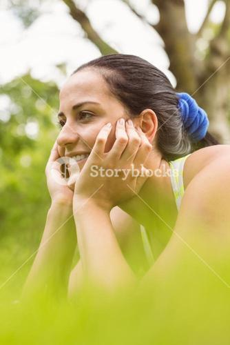 Smiling fit brunette relaxing and thinking on grass