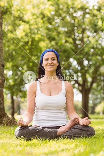 Smiling brunette in lotus pose on grass