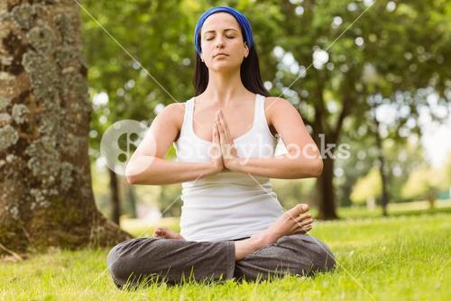 Brunette sitting in lotus pose with hands together