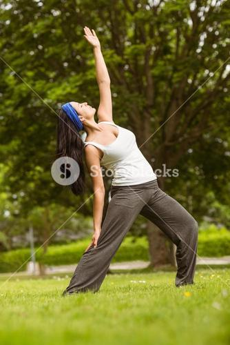 Cheerful brown hair doing yoga on grass