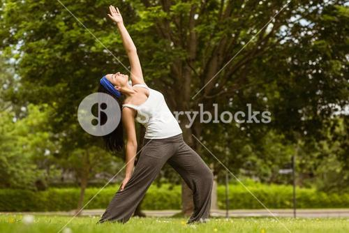 Peaceful brunette doing yoga in the park
