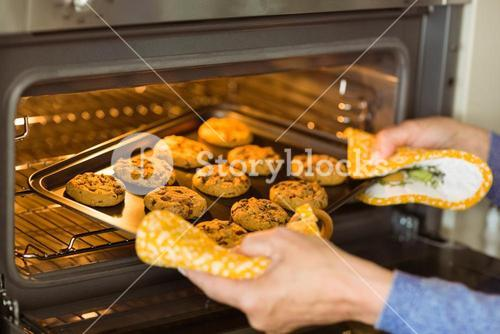 Woman taking tray of fresh cookies out of oven
