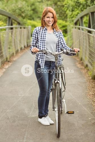 Pretty redhead with her bike smiling at camera