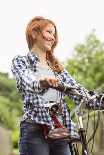 Readhead standing next to her bike with a camera