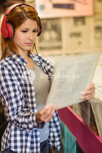 Girl looking for vinyl while listening to music
