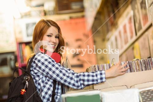 Pretty redhead searching a vinyl and smiling at camera