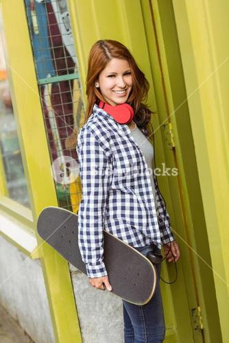 Redhead standing with his skateboard smiling at camera
