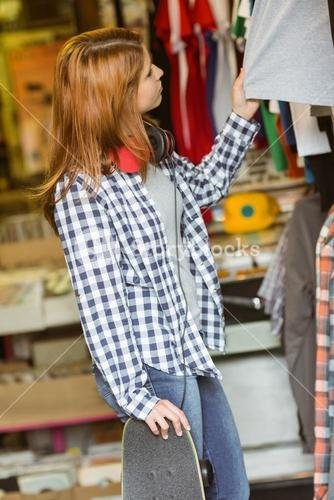 Girl looking at clothes while holding her skateboard