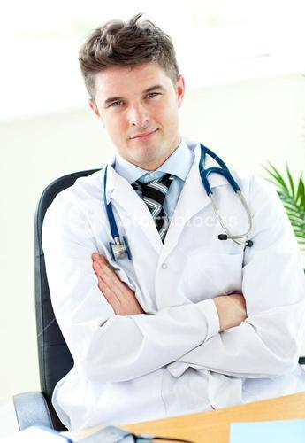 Portrait of a confident male selfassured doctor holding a stethoscope against a white background