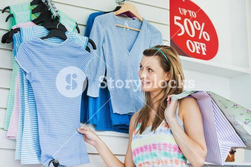 Delighted woman choosing clothes