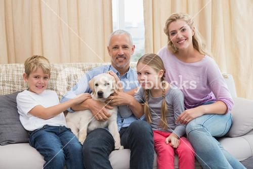 Parents with their children on sofa playing with puppy