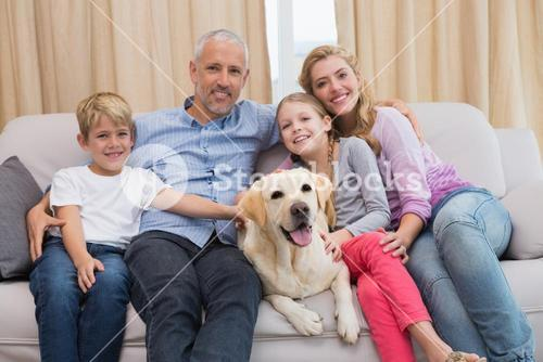 Parents and their children on sofa with labrador