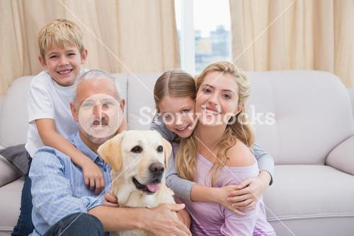 Parents and children on rug with labrador